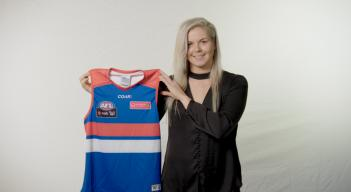 Katie holding a Western Bulldogs Jumper