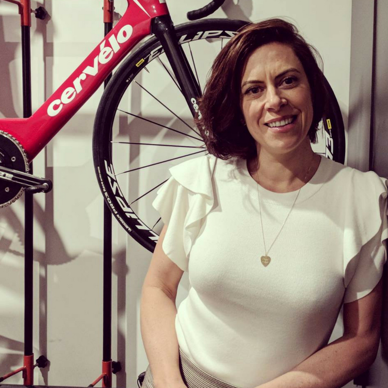 Bridie O'Donnell leaning against a wall with a bike in the background